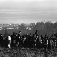 Allen Ginsberg speaking in a meadow: audience, with the city of Santa Cruz, the Monterey Bay, and a naval ship in the distance. 1967.