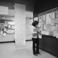 College Eight: student in a hallway with notice boards. 1979.